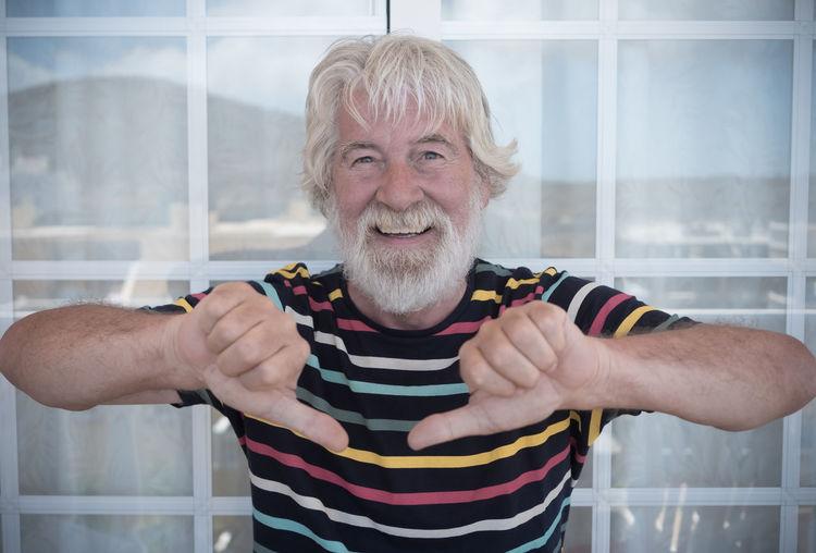 Portrait of cheerful bearded senior man gesturing against windows on balcony