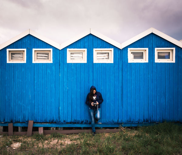 Woman standing against building against blue sky