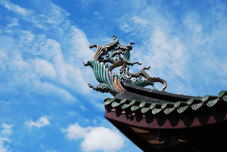 Low angle view of sculpture against blue sky