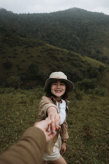Smiling woman holding cropped hand against mountain