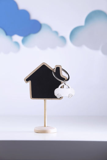 Close-Up Of Model Home With Clouds Against White Background