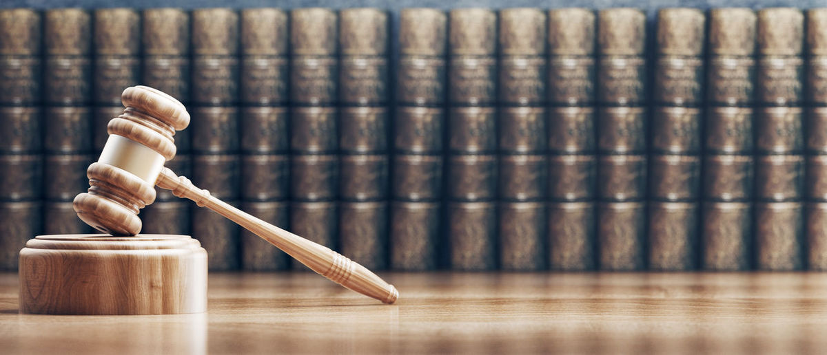 Close-up of wooden gavel against books on table