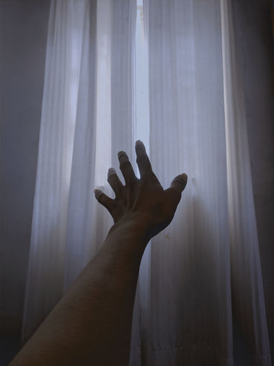 Close-up of hand against curtains at home