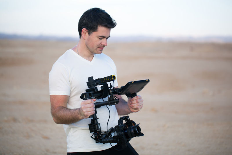 Beach Camera CameraMan Caucasian Electronic Gimbal Horizontal Man Outdoor Photo Photocamera Photographer Professional Record Shot Steadicam Steadycam Video Videographer Young