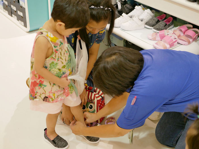 Asian mother's and the vendor's helping the little baby girl to put on shoes, trying them on before making a decision whether or not to buy them Child Childhood Females Real People Women Girls Lifestyles People Indoors  Casual Clothing Care Buy Putting On Try On Baby Feet Foot Shopping Shopping Mall Wear Relationship Mother Kid Toddler  Decide