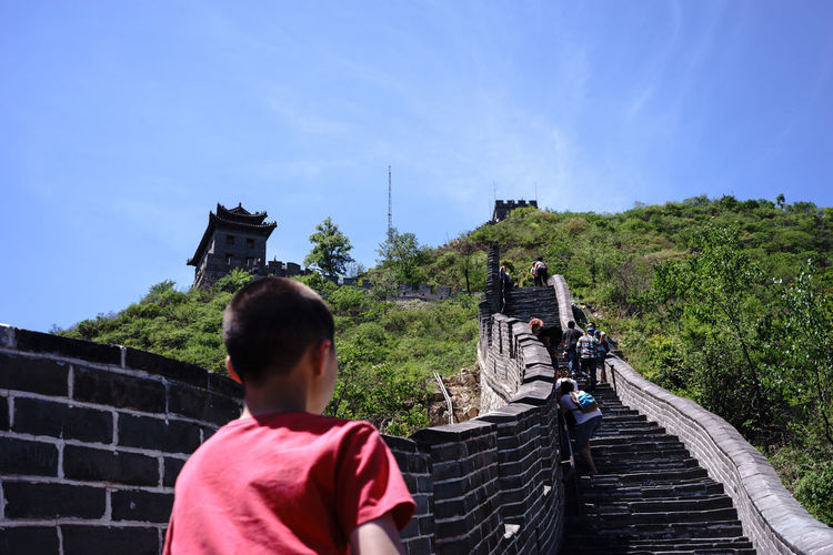 Boy climbing steps at great wall of china against sky
