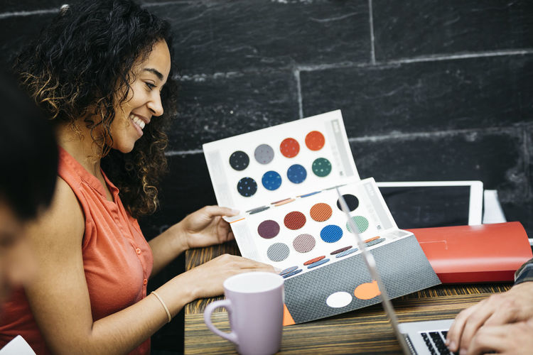 Smiling young woman holding color swatch in creative office