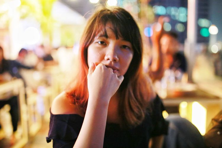 Portrait of woman eating food at restaurant looking straight to the camera