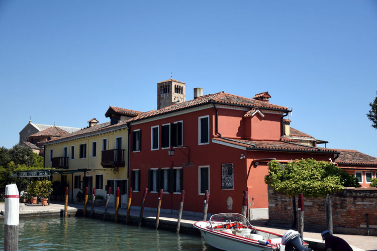View of buildings by canal against clear blue sky