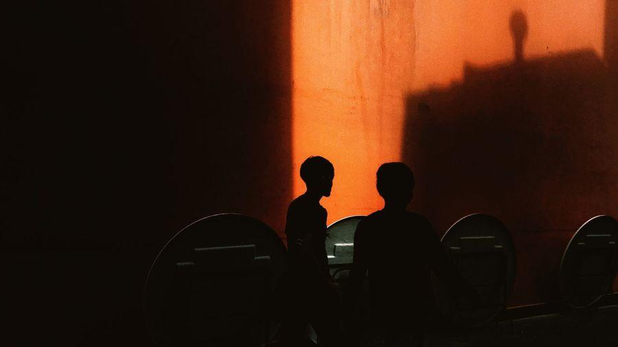Silhouette men standing against orange wall