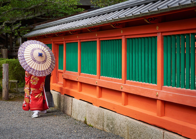 Woman in kimono with parasol standing outside a temple