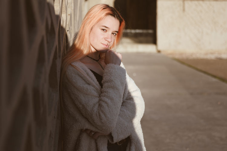 Portrait of young woman standing by wall