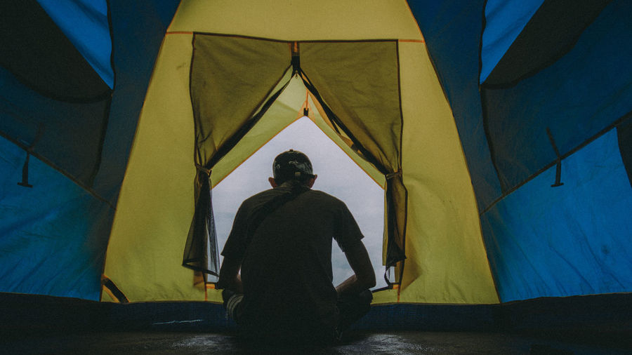 Rear view of man sitting at tent