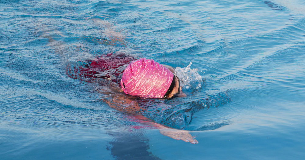 Close up of a women swimming laps directly at the camera in a pool wearing a pink bathing cap.