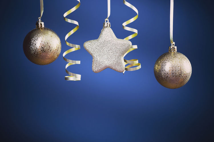 Close-up of christmas decoration hanging against blue background