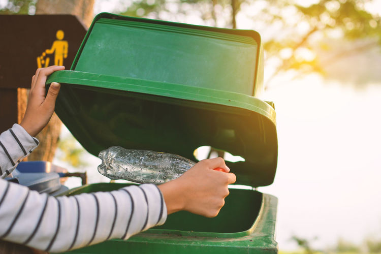 Cropped hand of woman putting plastic bottle in garbage can