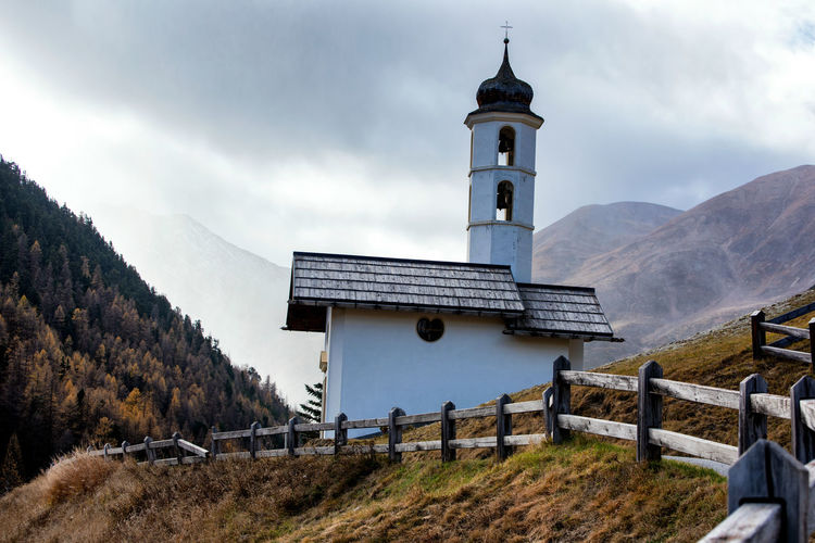 Church tower on building by mountains against sky
