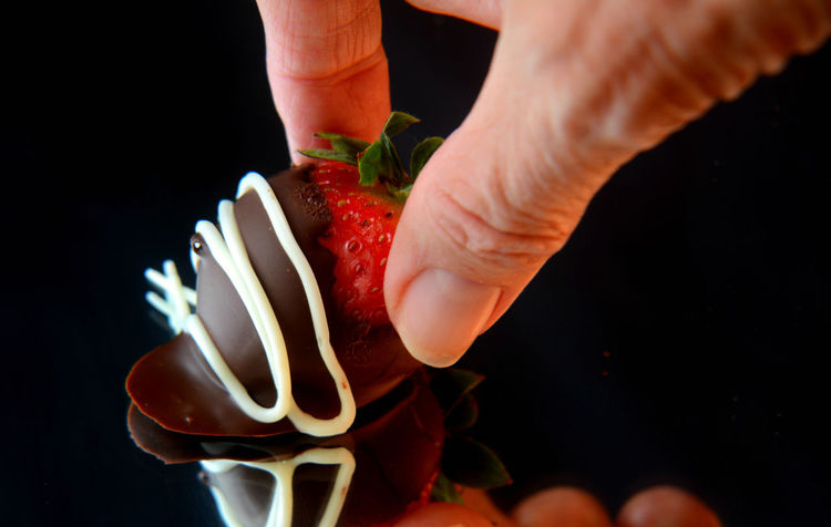 Black Background Chocolate Chocolate Covered Close-up Dessert Food Food And Drink Freshness Fruit Human Hand Ready-to-eat Reflection Strawberry Sweet Food Temptation Visual Feast