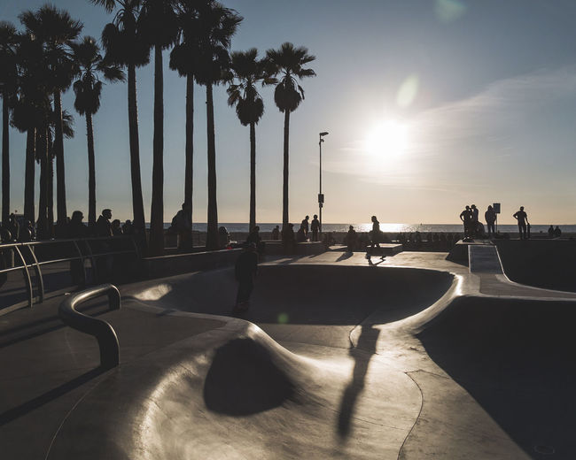 People in skateboard park against sea and sky during sunset