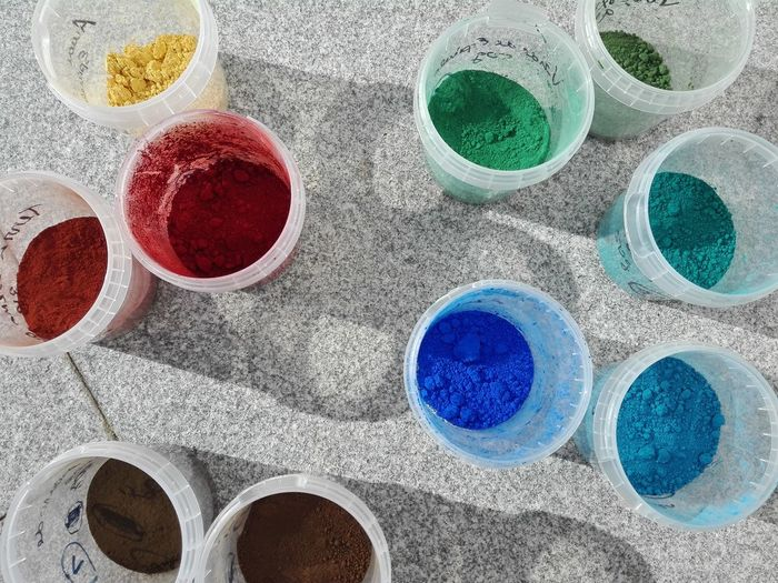 High angle view of colorful powder paints in containers on walkway