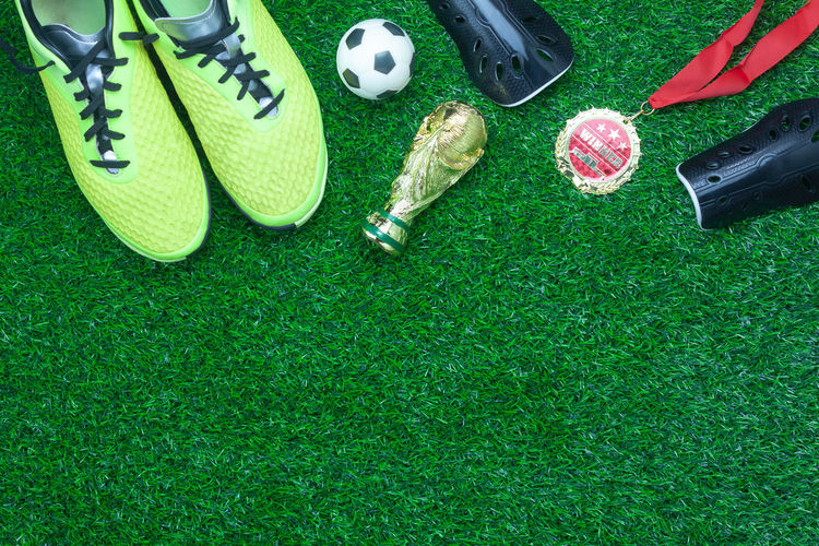 Ball Close-up Day Equipment Field Grass Green Color High Angle View Medium Group Of Objects Nature No People Outdoors Plant Shoe Soccer Sport Sports Equipment Still Life Team Sport Toy