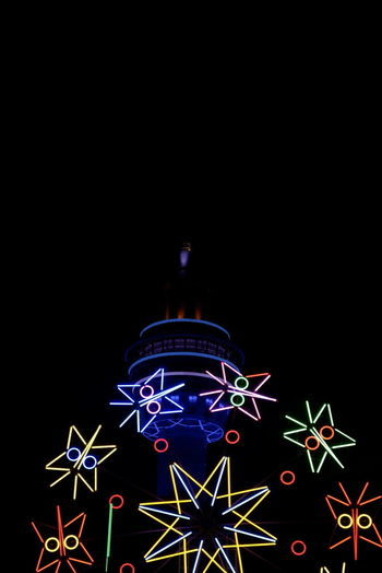 Illuminated christmas lights against sky at night