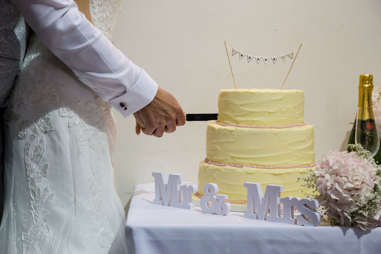 Midsection Of Couple Cutting Cake At Table