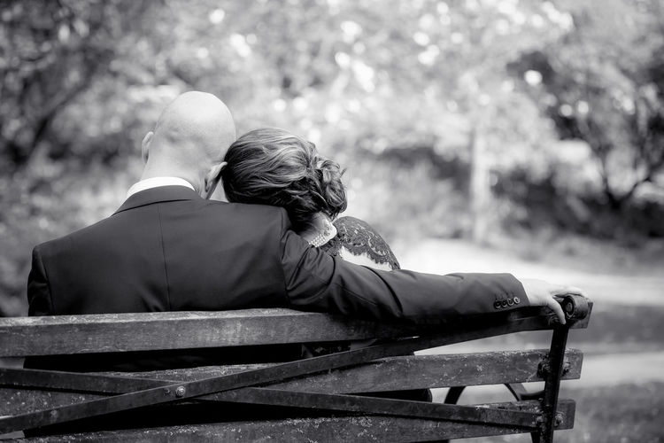 Rear View Of Couple Sitting On Bench At Park