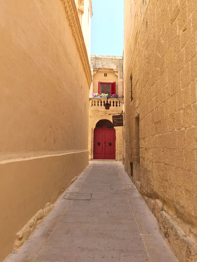 Narrow alley with red door at the end in Rabat, Malta Alley Alleyway Architecture Building Exterior Built Structure Day Narrow Alley No People Outdoors Red Door The Way Forward