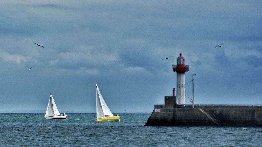 Lighthouse By Sailboats In Sea Against Cloudy Sky