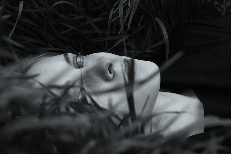 Portrait of woman lying down on grass