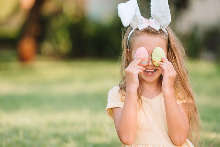 Smiling girl holding eggs outdoors