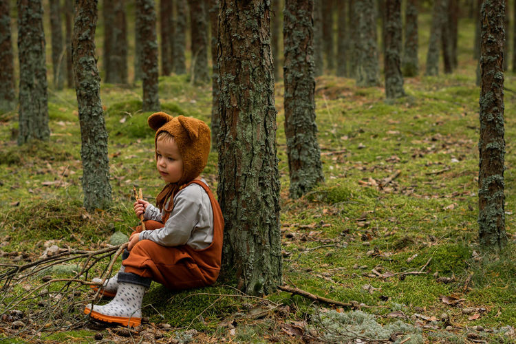 Toddler baby boy in bear bonnet sitting in the woods