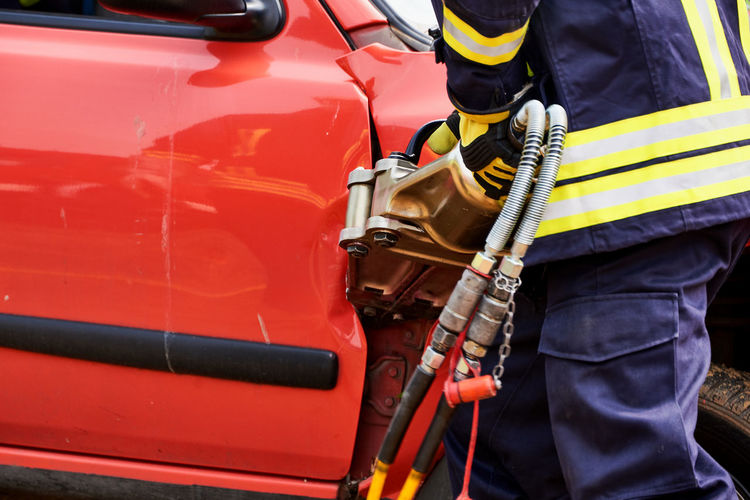 Midsection of firefighter working on car