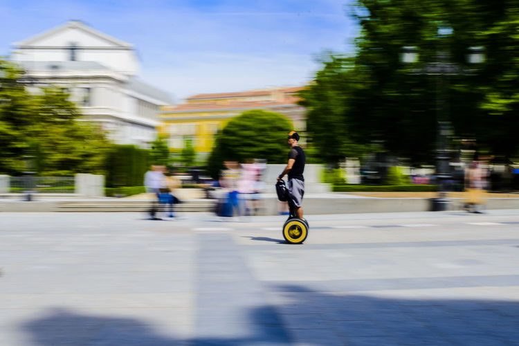 Blurred motion image of a man riding a segway in the Plaza de Oriente in Madrid. Balance Blurred Motion Built Structure City Day Destination Editorial  Leisure Activity Lifestyles Man Men Motion Movement Outdoors People Personal Transport Plaza De Oriente Real People Riding Segway Skill  Sunlight Transportation Travel Travelling