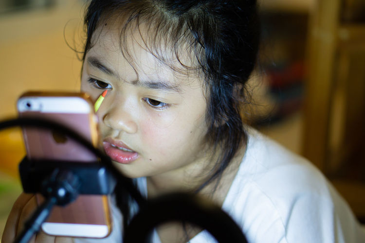 Portrait of girl looking through mobile phone