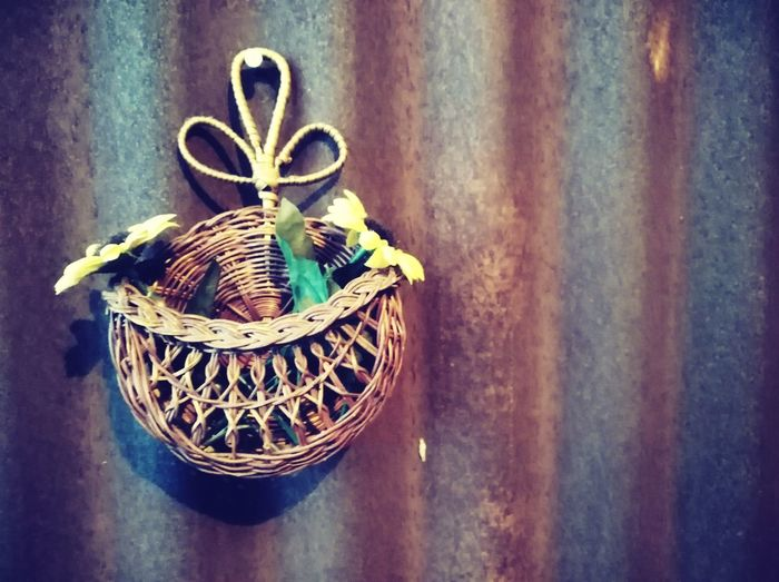 Close-up of wicker basket on table against wall