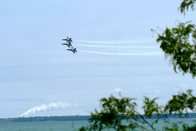 Low angle view of airshow flying over sea against sky