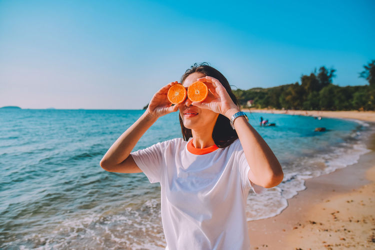 Close-up of smiling woman holding orange fruits at beach