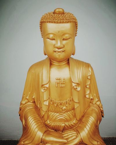 Close-up of buddha statue against building