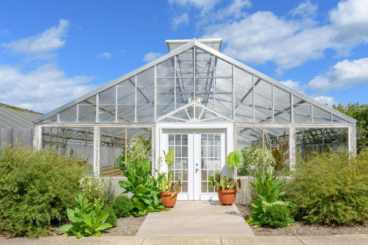 Garden greenhouse set up with white chairs for an event, against beautiful blue sky Beautiful Sky Event Gardening Wedding Venue Architecture Blue Botanical Garden Building Exterior Built Structure Cloud - Sky Day Garden Garden Greenhouse Greenhouse Growth Outdoors Plant Plant Nursery Potted Plant Sky Structure Windows