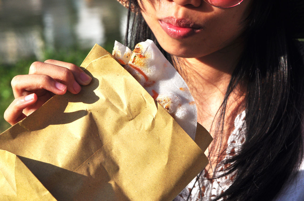 Midsection Of Woman Having Food On Sunny Day