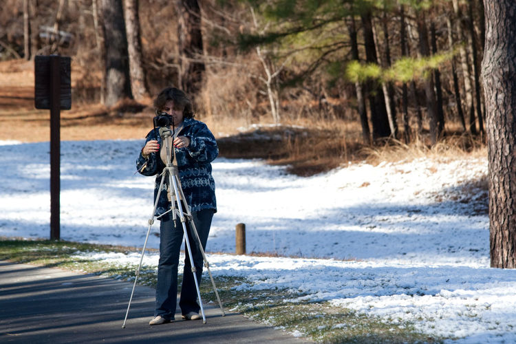 Full length of woman photographing with camera on tripod at forest during winter