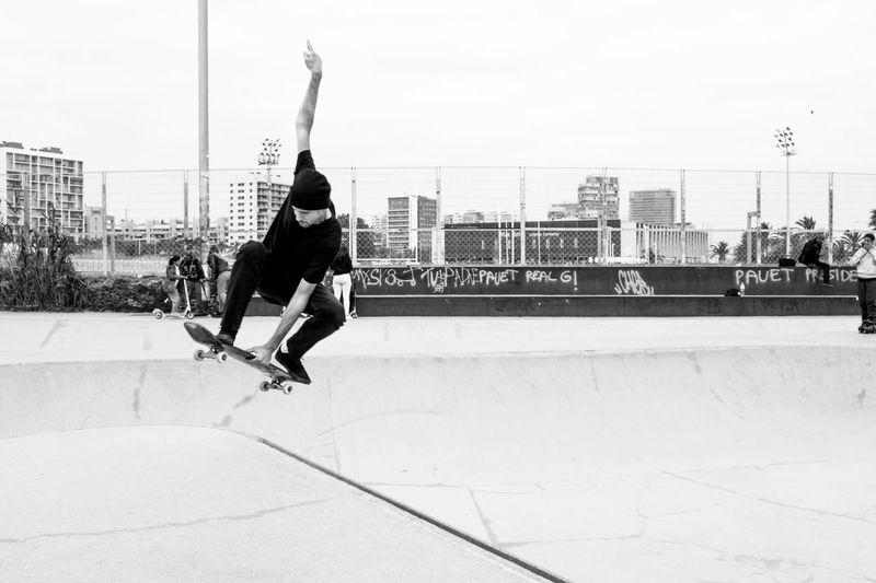 Full length of man jumping in city against sky