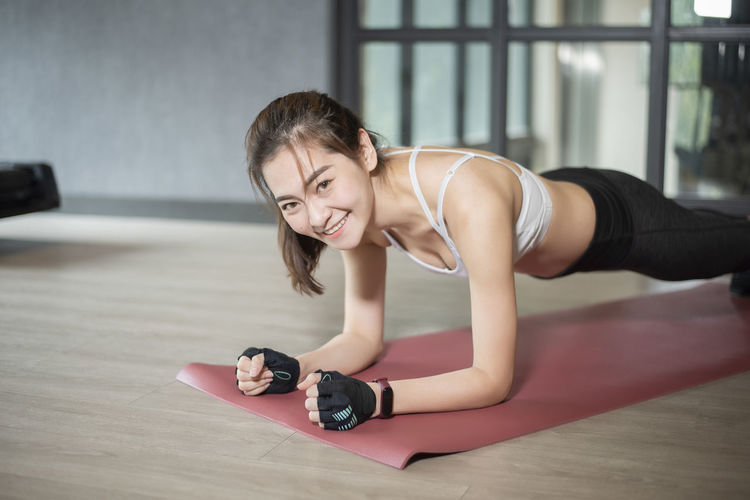 Portrait of young woman exercising on floor at gym