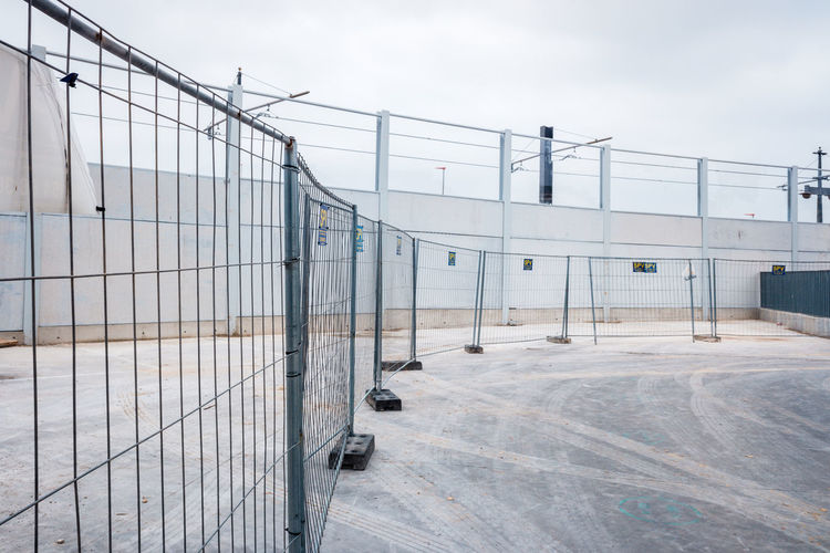Metal fence by building against sky