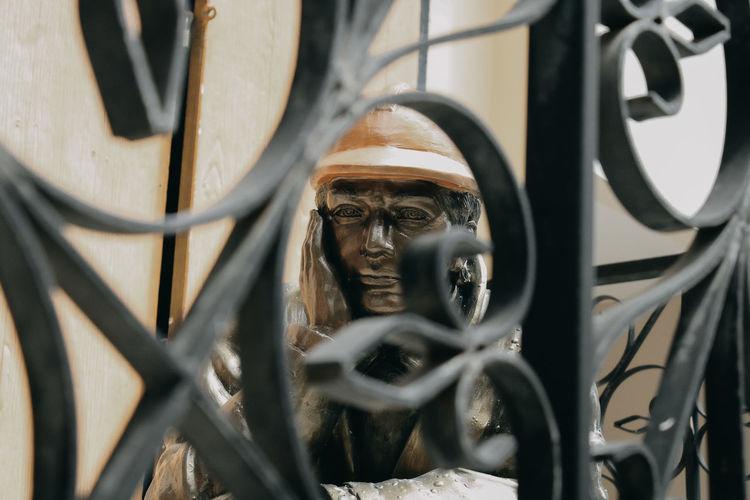 Sculpture seen through metal fence
