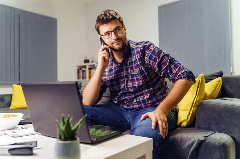Young man using mobile phone while sitting on sofa