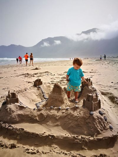 Boy playing with sand castle at beach against sky