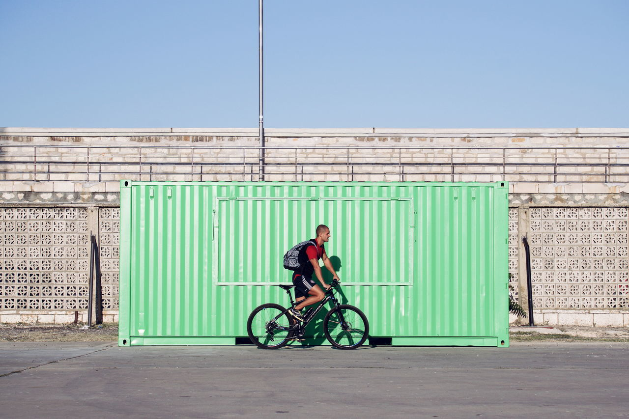 Side view of young man riding bicycle on wall